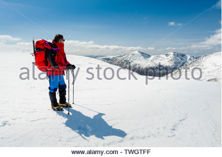 Winter mountaineering in the Cairngorms National Park, Scotland, with Cairn Toul and Angel's Peak on the horizon. - Stock Photo