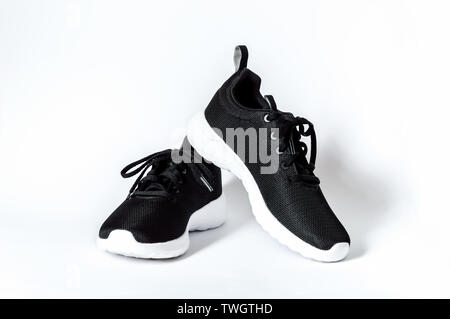 Black sports running shoes with white sole isolated on white background. Concept of fitness and healthy lifestyle - Stock Photo