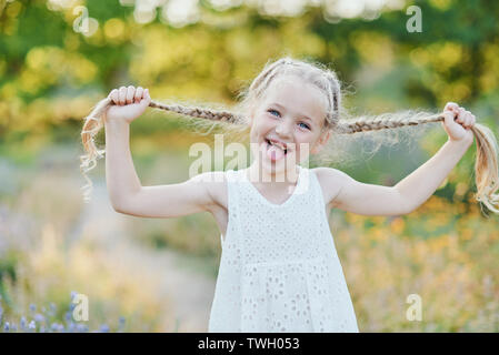 Funny girl holding hair plaits. Small cute girl with long blonde hair showing tongue outdoor. Kid expressing emotions. April fool - Stock Photo