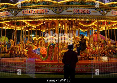 Man watching a vintage Fairground Carousel ride at night,York,Knavesmire,North Yorkshire,England. - Stock Photo