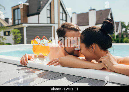 happy heterosexual couple is well rested with cocktails while in the pool. Summer rest - Stock Photo