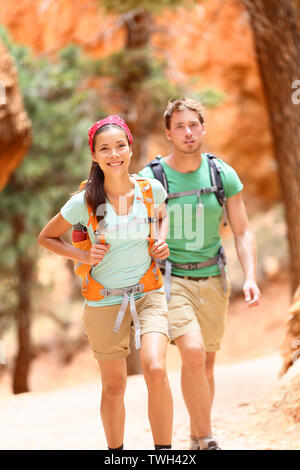 People hiking - couple hikers in Bryce Canyon walking smiling happy together. Multiracial couple, young Asian woman and Caucasian man in Bryce Canyon National Park landscape, Utah, United States. Stock Photo