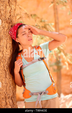 Dehydration thirst heat stroke exhaustion concept with woman hiker tired, dehydrated and exhausted Bryce Canyon. Girl tired close to heat stroke due to high temperature and lack of water. - Stock Photo