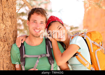 Hiking young couple portrait of happy hikers in Bryce Canyon walking smiling happy together. Multiracial couple, young Asian woman and Caucasian man in love, Bryce Canyon National Park landscape, Utah Stock Photo