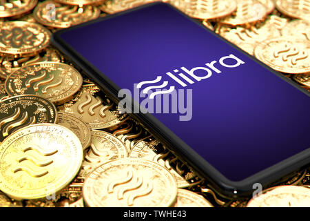 WROCLAW, POLAND - JUNE 20th, 2019: Facebook announces Libra cryptocurrency. Smartphone withLibra logo on the screen is laying down on Libra concept co - Stock Photo