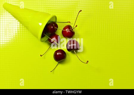 A plastic lime ice cream cone on the left top with red fresh sweet cherries scattered on the center on a plastic glossy background. View from above. - Stock Photo