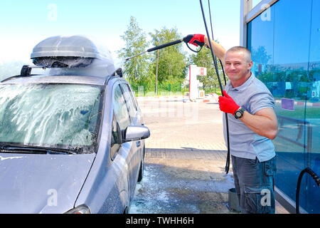 Man pours active foam car body. Car wash. Self-service washing complex. High pressure car wash - Stock Photo