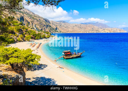 Tourist boat anchoring at beautiful Apella beach on Karpathos island, Greece - Stock Photo
