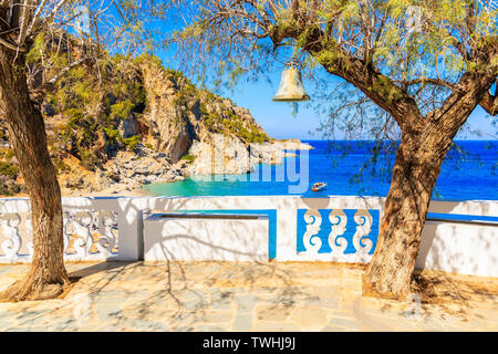 Bell hanging on tree and view of Kyra Pynagia beach from church terrace on Karpathos island, Greece - Stock Photo