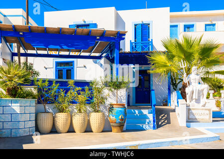 Sculpture of Poseidon, god of the sea in ancient Greek religion and myth in front of typical buildings in Finiki port, Karpathos island, Greece - Stock Photo