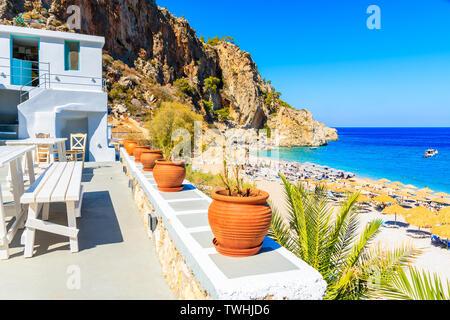 Flowerpots and taverna buildings on Kyra Pynagia beach, Karpathos island, Greece - Stock Photo