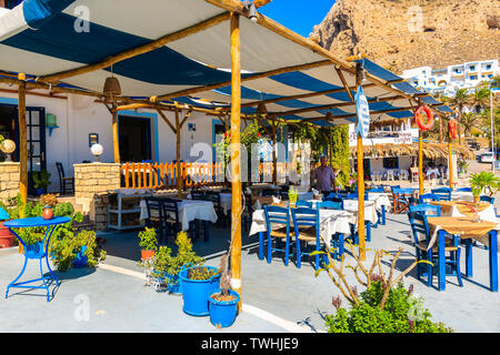 FINIKI PORT, KARPATHOS ISLAND - SEP 25, 2018: View of taverna restaurant in small fishing village on coast of Karpathos island, Greece. - Stock Photo