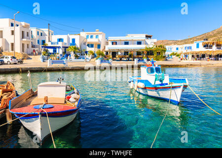 Fishing boats in picturesque Finiki port with colorful tavernas in background, Karpathos island, Greece - Stock Photo