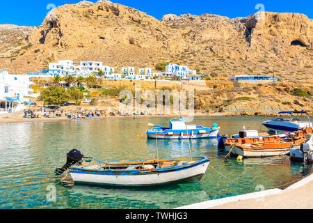 Fishing boats in picturesque Finiki port with mountains in background, Karpathos island, Greece - Stock Photo