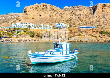 White typical fishing boat on turquoise sea water in Finiki port, Karpathos island, Greece - Stock Photo