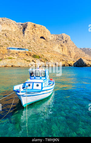 Fishing boat in picturesque Finiki port with mountains in background, Karpathos island, Greece - Stock Photo