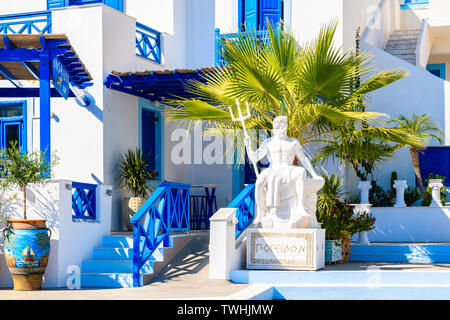 FINIKI PORT, KARPATHOS ISLAND - SEP 25, 2018: Sculpture of 'Poseidon' - god of the sea in ancient Greek religion and myth in front of typical building - Stock Photo