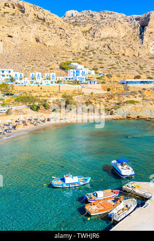 Fishing boats on turquoise sea water in Finiki port, Karpathos island, Greece - Stock Photo