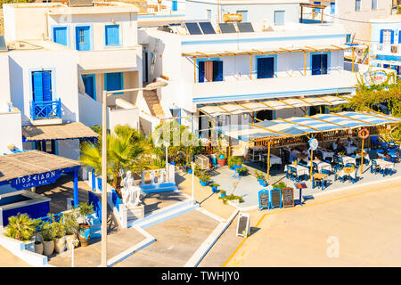 FINIKI PORT, KARPATHOS ISLAND - SEP 25, 2018: View of taverna restaurant and white houses in small fishing village on coast of Karpathos island, Greec - Stock Photo