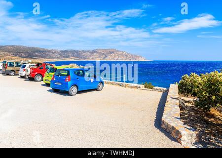 KARPATHOS ISLAND, GREECE - SEP 26, 2018: Rental cars parking on viewpoint on Karpathos island near Ammopi village, Greece. - Stock Photo