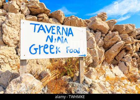 AMMOPI VILLAGE, KARPATHOS ISLAND - SEP 26, 2018: White sign of Greek taverna in front of rocks on coastal path in Ammopi village. Greek islands are fa - Stock Photo