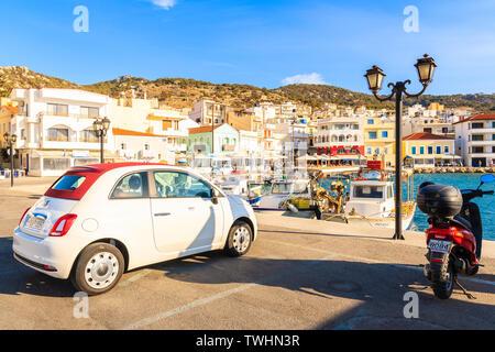 PIGADIA PORT, KARPATHOS ISLAND - SEP 26, 2018: Stylish Fiat 500 parking in picturesque Pigadia port on Karpathos island at sunset time, Greece. - Stock Photo