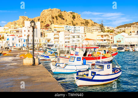 Fishing boats in picturesque Pigadia port at sunset time, Karpathos island, Greece - Stock Photo