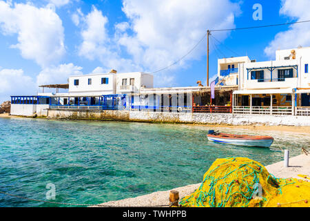 Fishing nets and boat in Lefkos port with typical Greek houses on shore, Karpathos island, Greece - Stock Photo