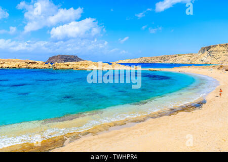 Unidentified man walking on beautiful beach with amazing sea colors in Lefkos village on coast of Karpathos island, Greece - Stock Photo