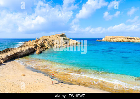 Young woman standing on beautiful beach with amazing sea colors in Lefkos village on coast of Karpathos island, Greece - Stock Photo