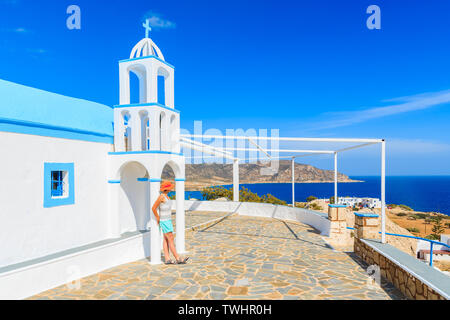 Young woman tourist standing on terrace of traditional white church in Ammopi village, Karpathos island, Greece - Stock Photo