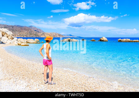 Young woman standing on Apella beach and looking at sea, Karpathos island, Greece - Stock Photo