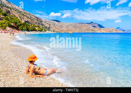Young woman relaxing in water on Apella beach, Karpathos island, Greece - Stock Photo