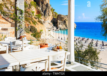 Tables in typical Greek taverna on Kyra Pynagia beach, Karpathos island, Greece - Stock Photo