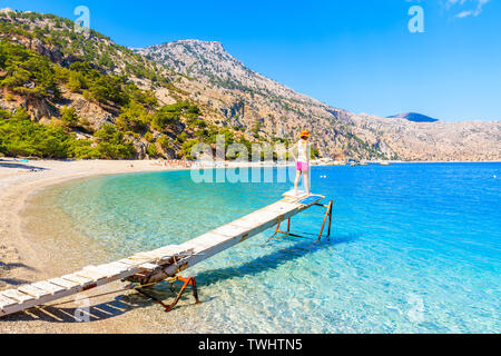 Young woman standing on small wooden jetty at Apella beach, Karpathos island, Greece - Stock Photo
