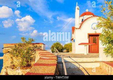 White church on high cliff above sea near Karpathos port, Karpathos island, Greece - Stock Photo