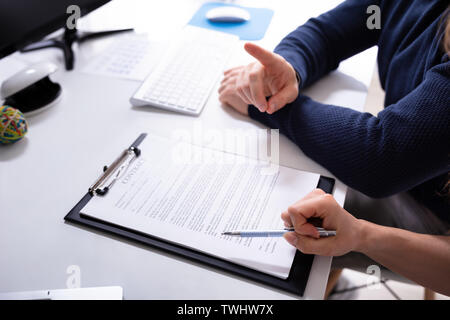 Human's Hand With Contract Agreement On Clipboard Over White Desk In Office - Stock Photo