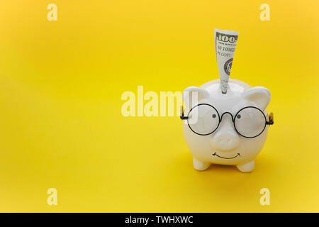 White piggy bank wearing a black glasses over yellow background