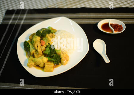 vegetarian curry on rice, setup nicely on a table ready to serve - Stock Photo