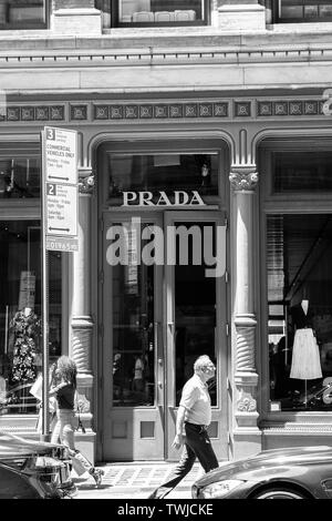 New York, 6/15/2019: People walk by a Prada store in SoHo. - Stock Photo