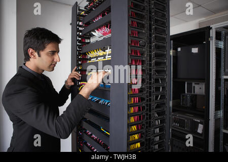 Technician working in a server room - Stock Photo