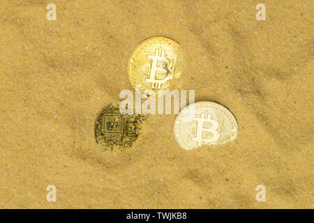 several bitcoin crypto coins on brilliant golden sand, top view. finding and mining cryptocurrency - Stock Photo