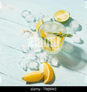 A drink of lemon and lime in an elegant glass on a blue background with bright sunshine. Summer cocktail or mojito.