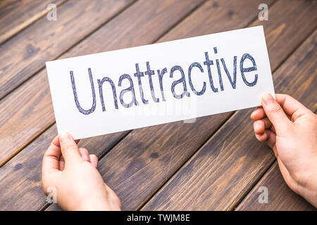hands hold white paper with word unattractive - Stock Photo