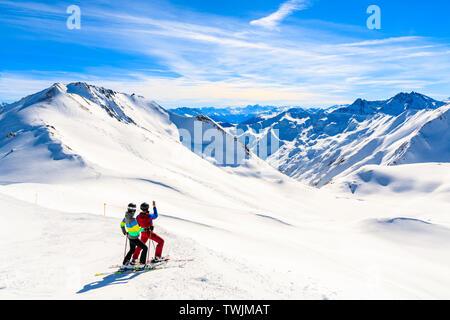 Couple of skiers taking photo on slope with amazing view of Austrian Alps mountains in beautiful winter snow, Serfaus Fiss Ladis, Tirol, Austria - Stock Photo