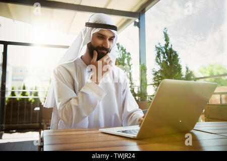 Arab saudi businessman working online with a laptop and tablet in a coffee shop or a cafe with an outdoor terrace in the background. Concept of business, finance, modern technologies, start up. - Stock Photo