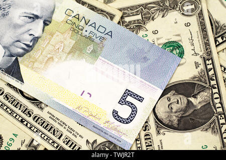 A macro image of a blue Canadian five dollar bill on a background of American one dollar bills close up - Stock Photo