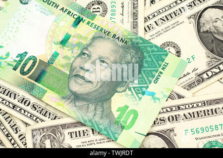 A close up image of a green ten rand bank note from South Africa in macro on a bed of American one dollar bills - Stock Photo