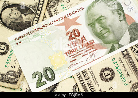 A close up image of a green twenty Turkish lira bank note on a background of American one dollar bills in macro - Stock Photo