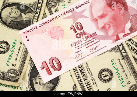 A close up image of a red ten Turkish lira bank note on a background of American one dollar bills in macro - Stock Photo